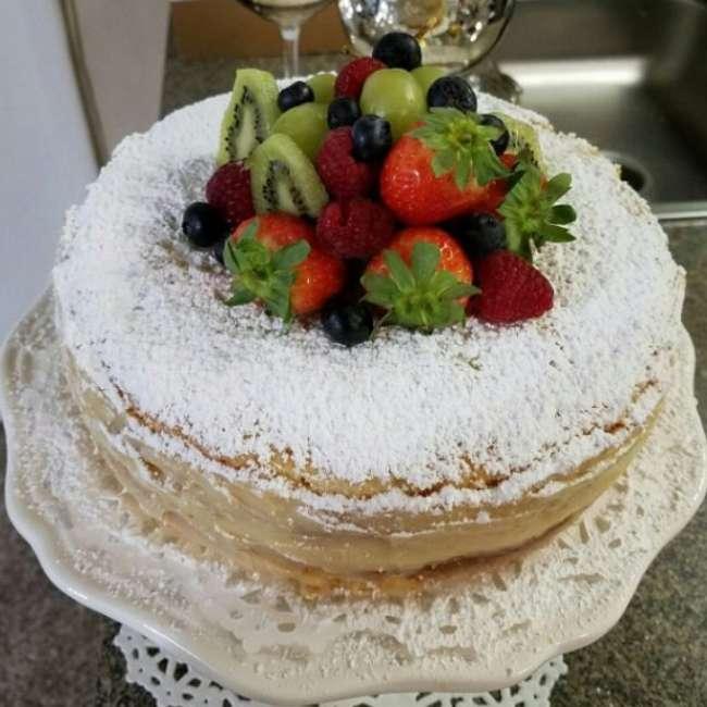 receita de bolo bem casado fofinho coberto com açúcar de confeiteiro e decorado com morangos e kiwis